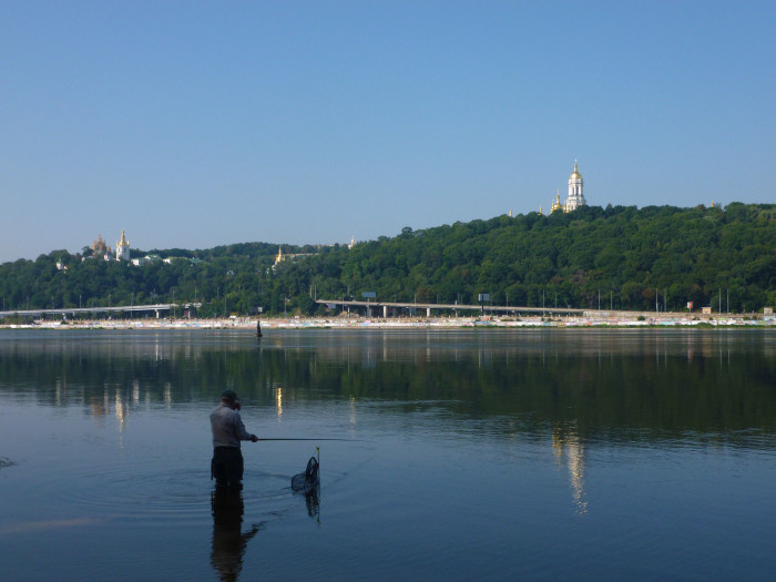 A man fishin in the Dnipro River that bisects Kiev.