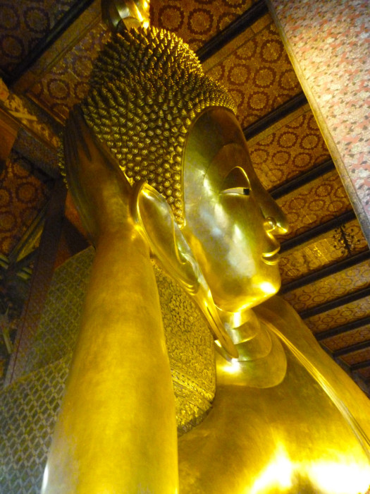 The reclining Buddha of Wat Pho. I don't know how many Buddha statues I've seen between the years I spent in China and the months I've spent in Southeast Asia, but I thought that this was one of the coolest I've seen. It's huge. Much bigger than I thought it would be. I was standing straight up when I took this photo. It's 50 ft (15 m) high and 141 ft (43 m) long.