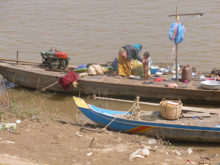 A mother and child on their boat in the river