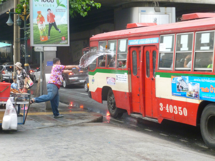 A guy trying to throw a bucket of water through a bus window in Bangkok. Brutal.