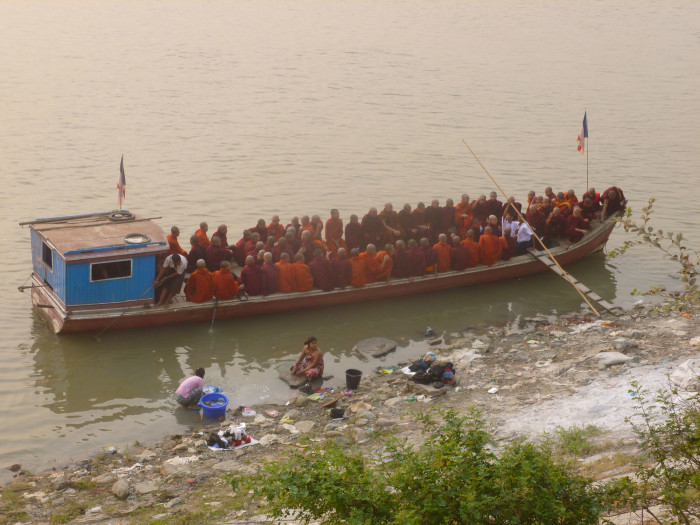Monks getting into a boat to cross the Irrawaddy River.