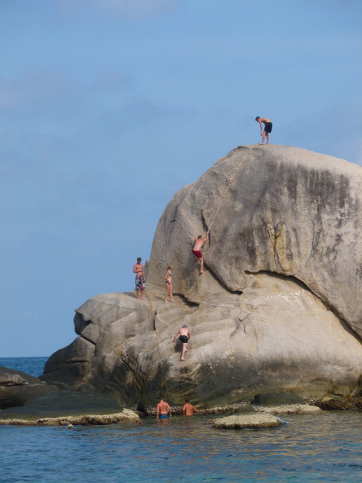 Climbing up the sketchy rope to the top of the cliff jumping rock in Tanote Bay